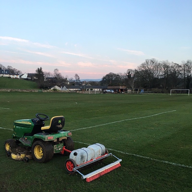 tractor and attachment brushing the pitch